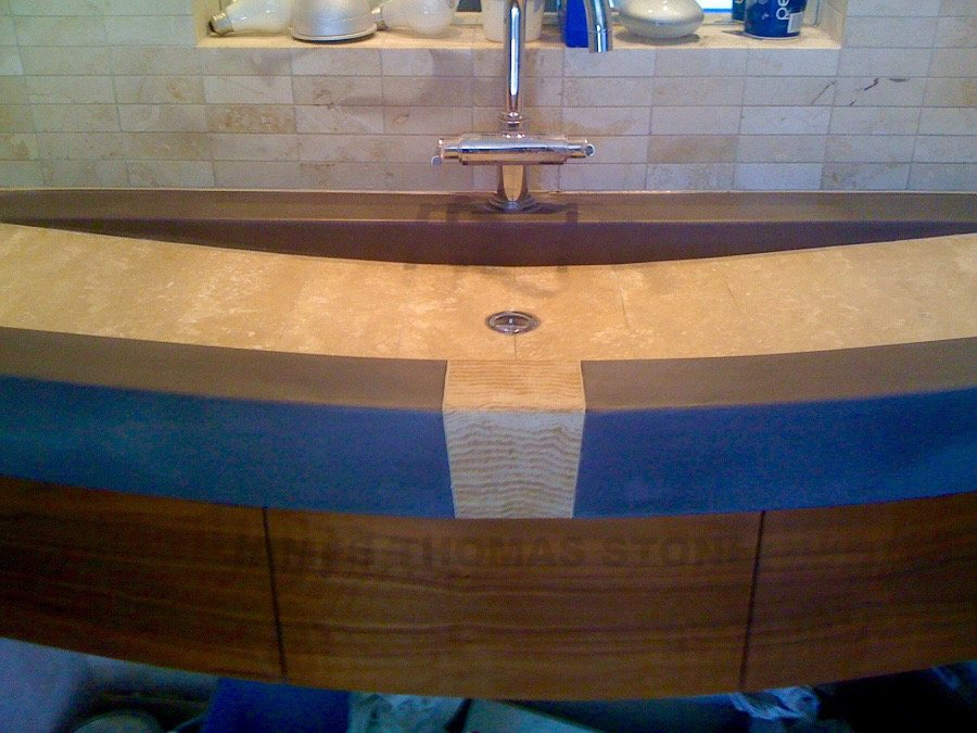 custom molded concrete floating sink design with inlayed travertine